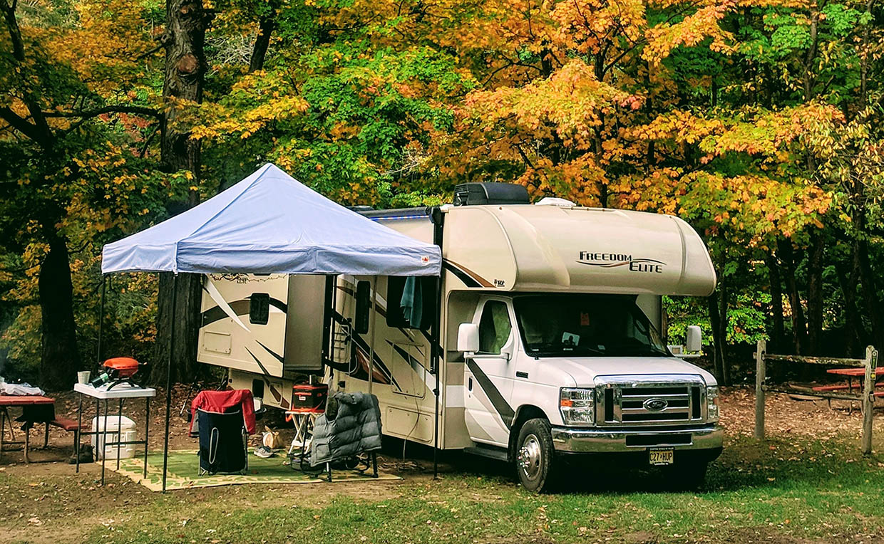 RV with tent cover on a river site in the fall