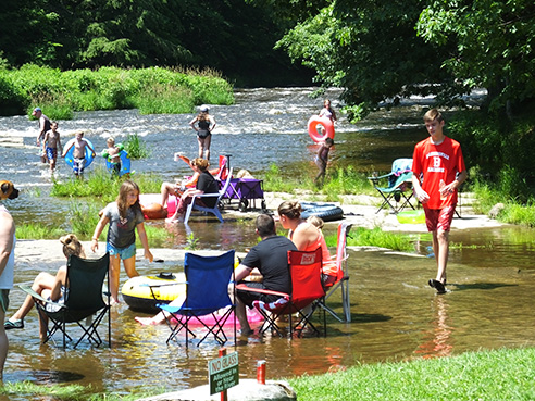 campers sitting in chairs in the river