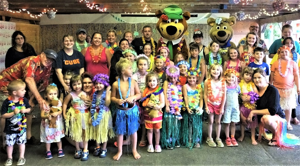 Photo of Yogi Bear and Cindy Bear with campers dressed in hawaiian outfits