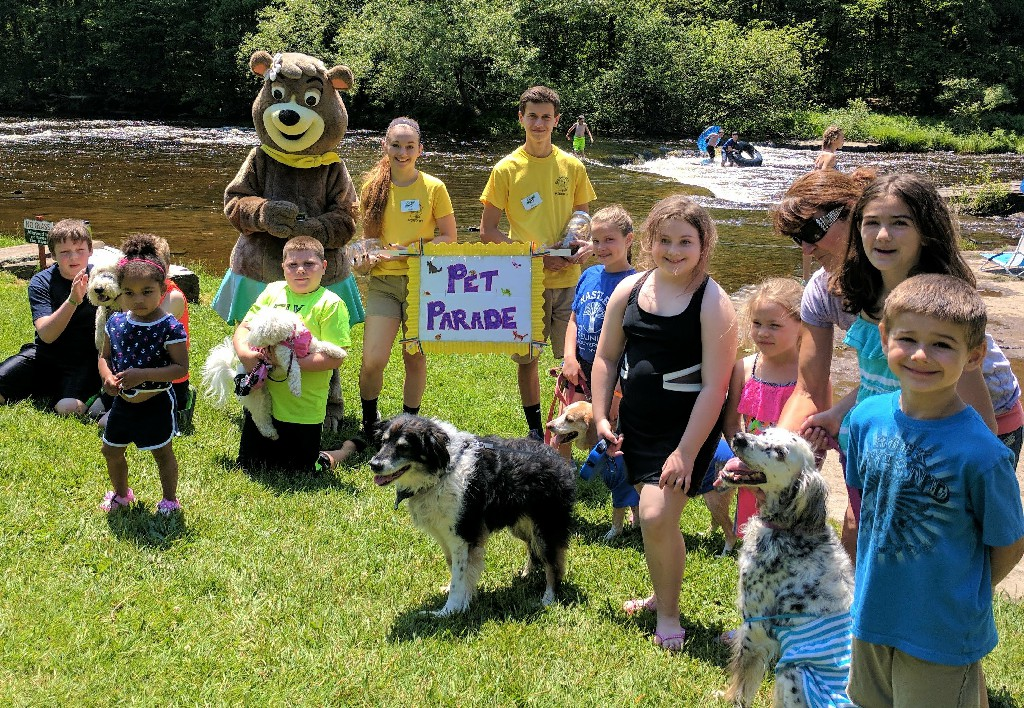 Cindy Bear and young campers with their pets for a parade