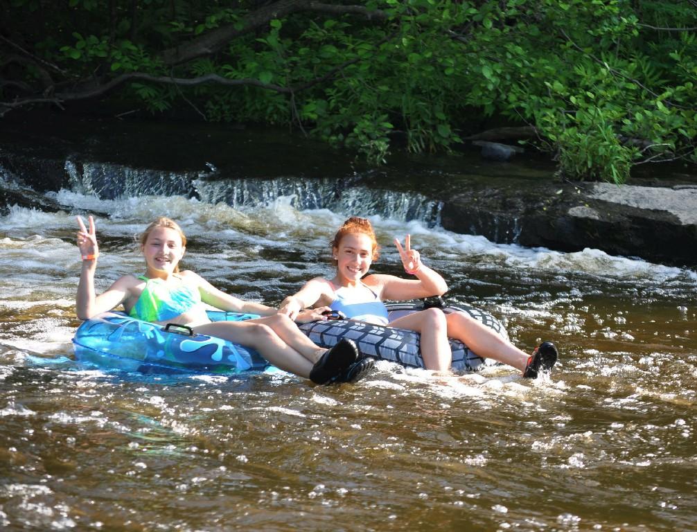 two girls floating in the river in innertubes